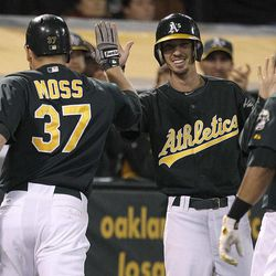 Oakland Athletics' Brandon Moss (37) is congratulated after hitting a two-run home run off Boston Red Sox's Alfredo Aceves in the inning of a baseball game Friday, Aug. 31, 2012, in Oakland, Calif.