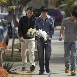 University of Southern California students bring flowers to the site of the slayings of their friends, two USC graduate students shot early Wednesday, April 11, 2012, in Los Angeles. Police said a gunman opened fire on a BMW near the University of Southern California campus on Wednesday, killing two international students from China in what may have been a bungled carjacking attempt.