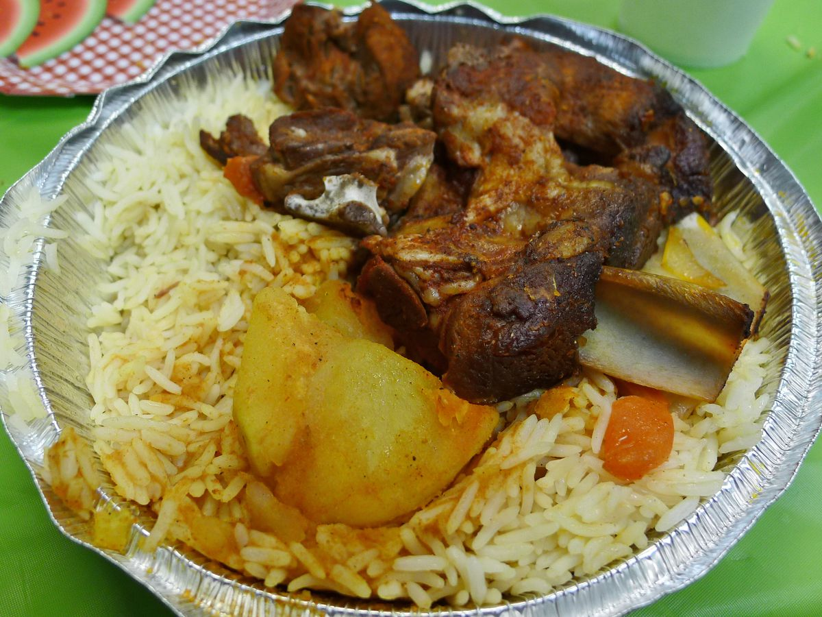 Lamb shank over rice in a carryout container.