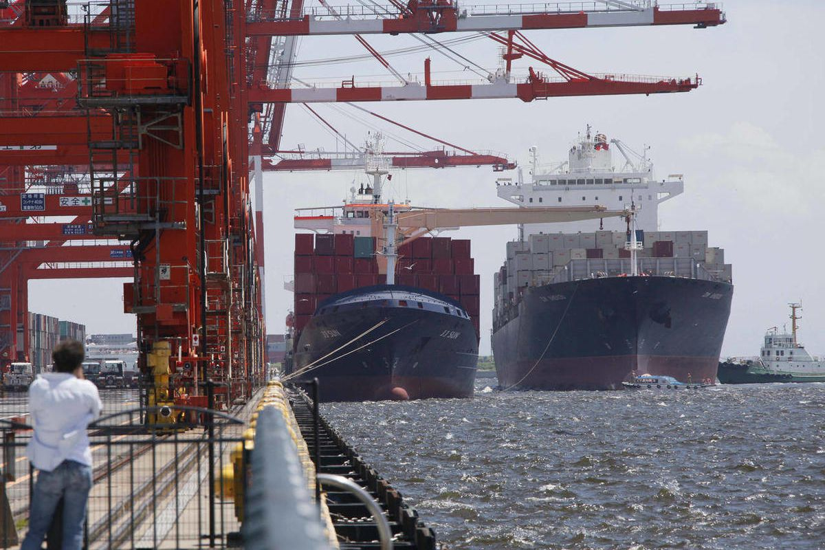 FILE - In this Aug. 13, 201 file photo, a container ship, right, arrives at a container terminal in Tokyo. Japan posted a smaller-than-expected trade deficit of $9.6 billion for August, as exports to Europe and other Asian countries plunged, further under