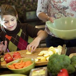 Sophia Udell, 7, cuts up vegetables for a pasta primavera salad that was to be donated to the OccupySLC demonstrators who are camped at Pioneer Park on Thursday, October 12, 2011.