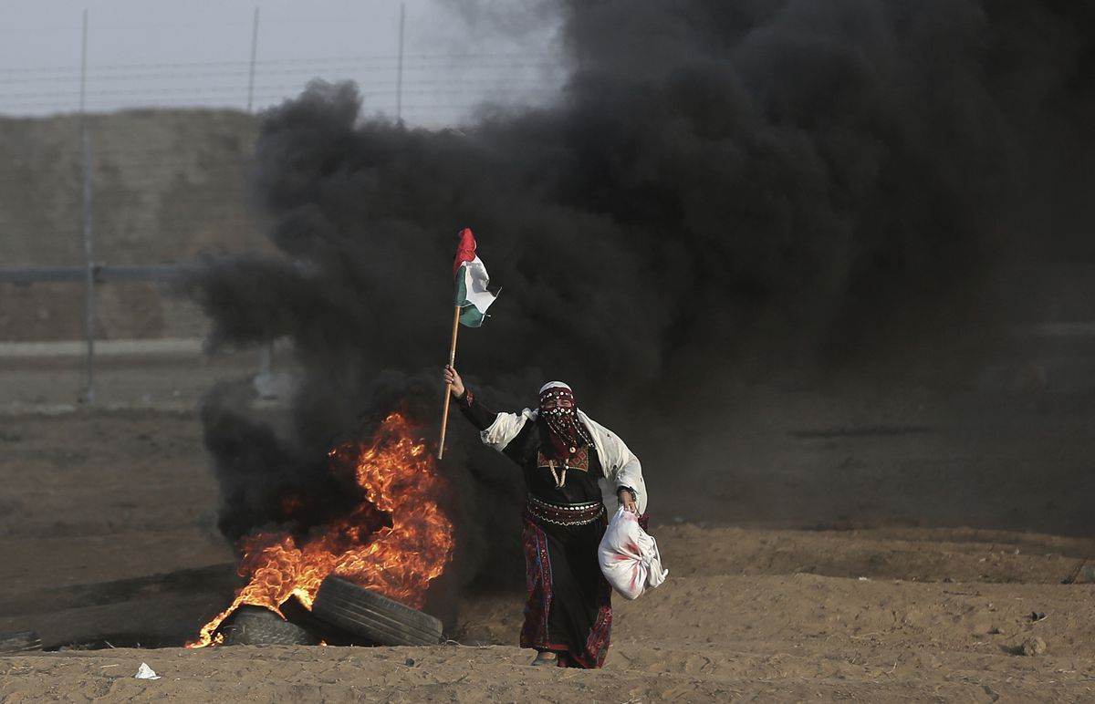 In this Oct. 5, 2018 file photo, a Palestinian woman wearing a traditional thobe, carries a Palestinian flag during a protest at the Gaza Strip's border with Israel. (AP Photo/Khalil Hamra, File)