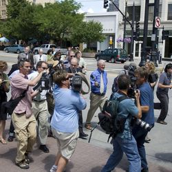 Members of the press swarm Tim DeChristopher as he arrives at the federal courthouse in Salt Lake City for his sentencing on Tuesday, July 26, 2011.