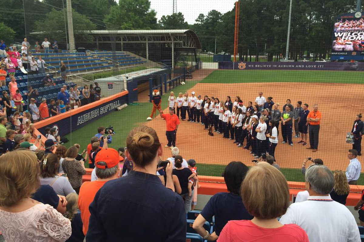 Coach Clint Myers addresses fans gathered to welcome the softball team home.