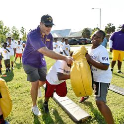 LSU offensive line coach Jeff Grimes works with kids at youth clinic. Thursday morning, BYU announced that it has hired Grimes to become the new offensive coordinator at BYU.