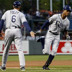 Tampa Bay Rays' B.J. Upton, right, high-fives third base coach Tom Foley as he rounds the bases after hitting a solo home run in the first inning of a baseball game against the Baltimore Orioles in Baltimore, Wednesday, Sept. 12, 2012.