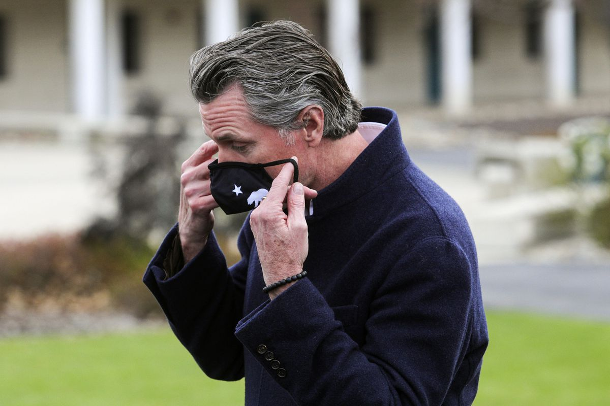 California Gov. Gavin Newsom puts his mask back on after delivering comments critical of other states that are dropping their masking requirements, Tuesday March 2, 2021, while visiting one of San Luis Obispo County's vaccination centers at Cuesta College.