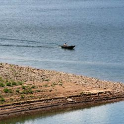 A boater moves across East Canyon Reservoir on Tuesday, June 25, 2013. Utah is facing drought conditions this summer.