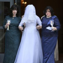 Sharonne Zippel, left, and Rosa Cohen, right, escort Chaya Zippel, the bride, during her wedding at the Grand America Hotel in Salt Lake City on Monday, Sept. 12, 2016. The bride wears an opaque veil in traditional Hassidic weddings to emphasize marrying for inner beauty.