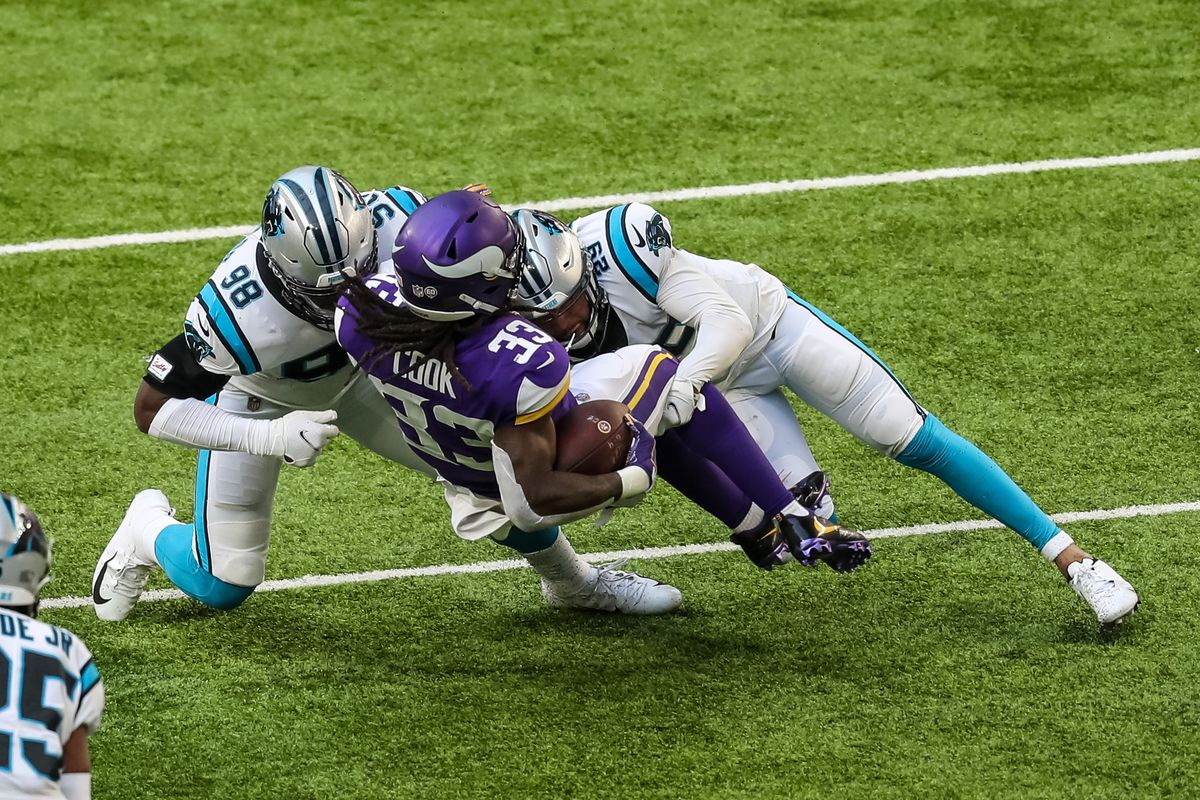 Minnesota Vikings running back Dalvin Cook (33) is tackled by Carolina Panthers defensive end Marquis Haynes (98) and cornerback Corn Elder (29) during the second quarter at U.S. Bank Stadium.