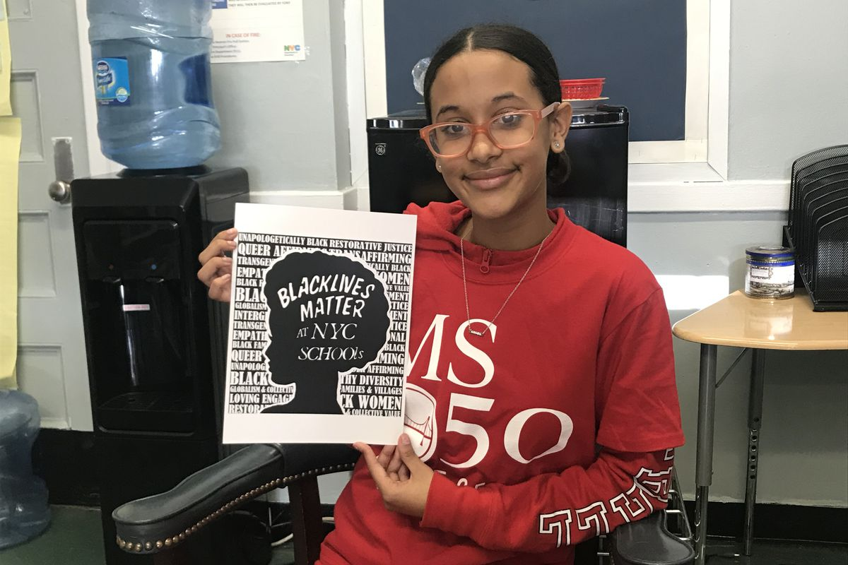 Emma Pichardo, a student at Brooklyn middle school, holds up her winning design for a Black Lives Matter t-shirt contest.