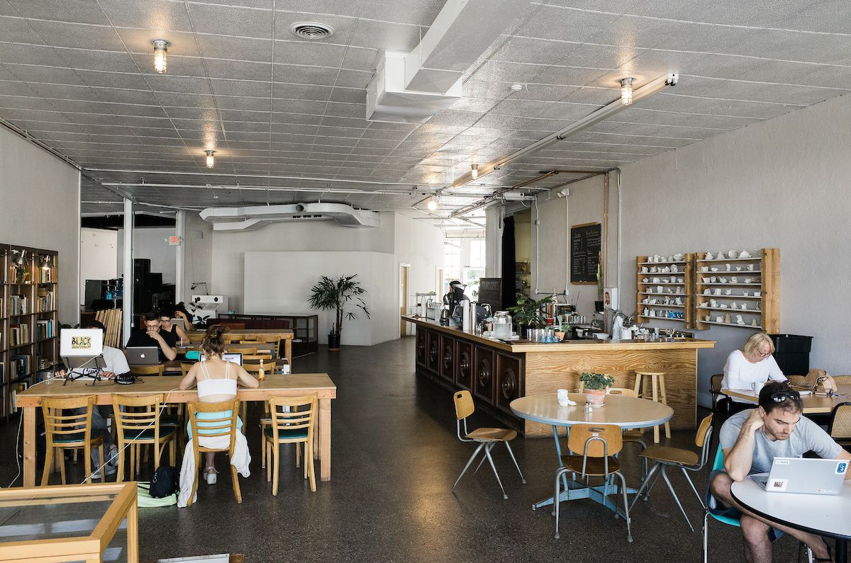 Customers sit in the white-boxed cafe space at Trinosophes.
