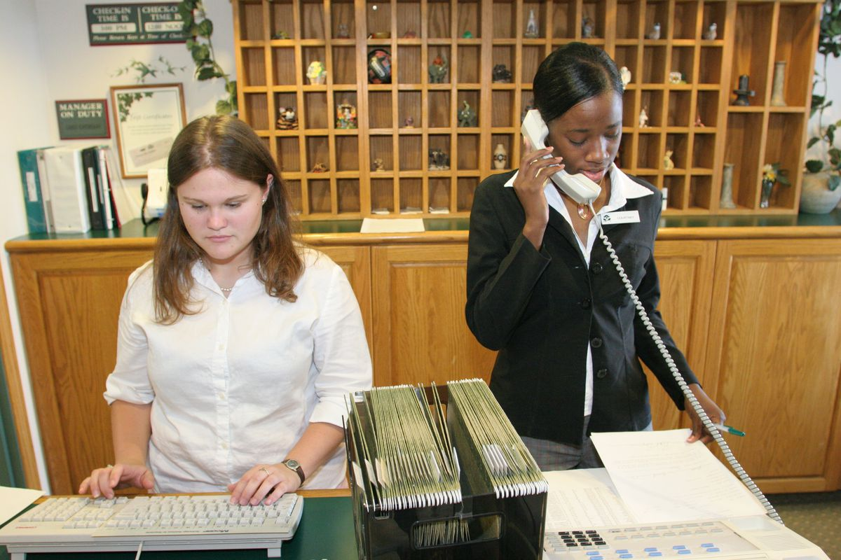 Two women employees behind the reception desk at Country Inn and Suites.