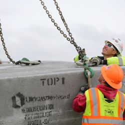 Workers install a concrete culvert to go under a temporary haul road for construction of the new prison in Salt Lake City on Wednesday, Feb. 22, 2017.