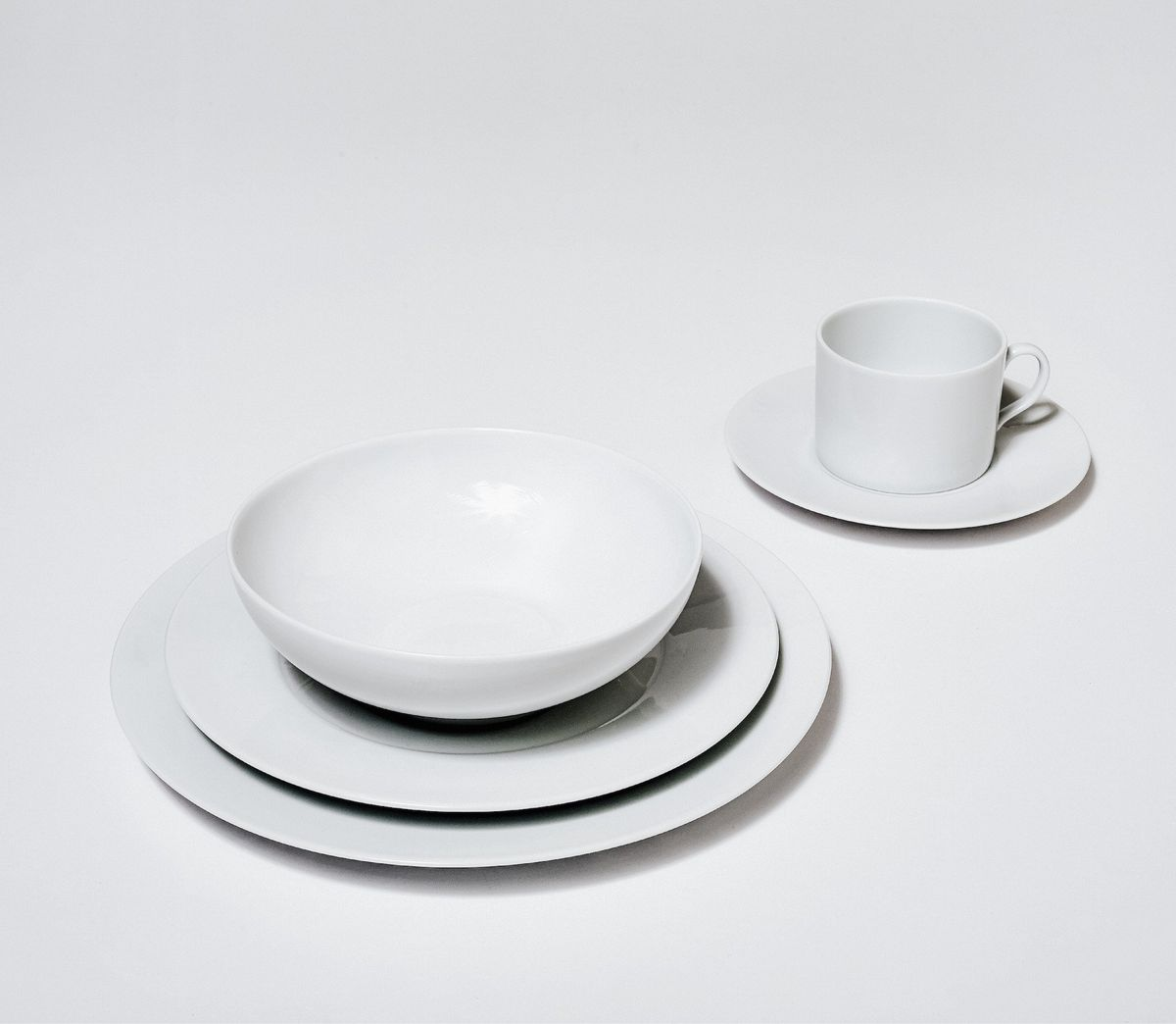 Two plates stacked under a bowl and a cup and saucer, all white, on a white background