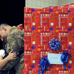 Air Force Tech Sgt. Edward Goettig hugs his daughter Olivia after she unwrapped her present on her 10th birthday to discover her dad inside, who returned home a week early, at Fox Hollow Elementary School in Lehi on Thursday, March 6, 2014. Goettig had been deployed to Afghanistan since Aug. 27, 2013.