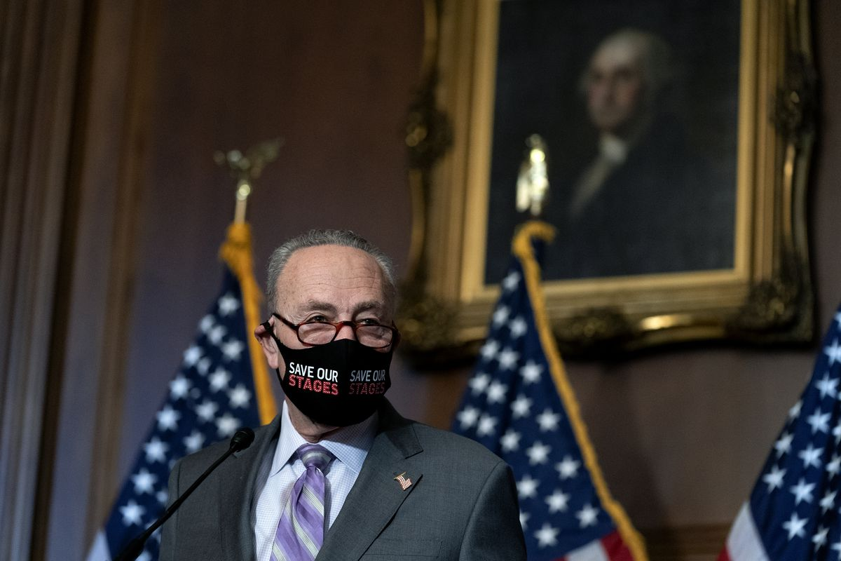 Senate Majority Leader Chuck Schumer smiles underneath a mask, standing in front of a row of US flags.