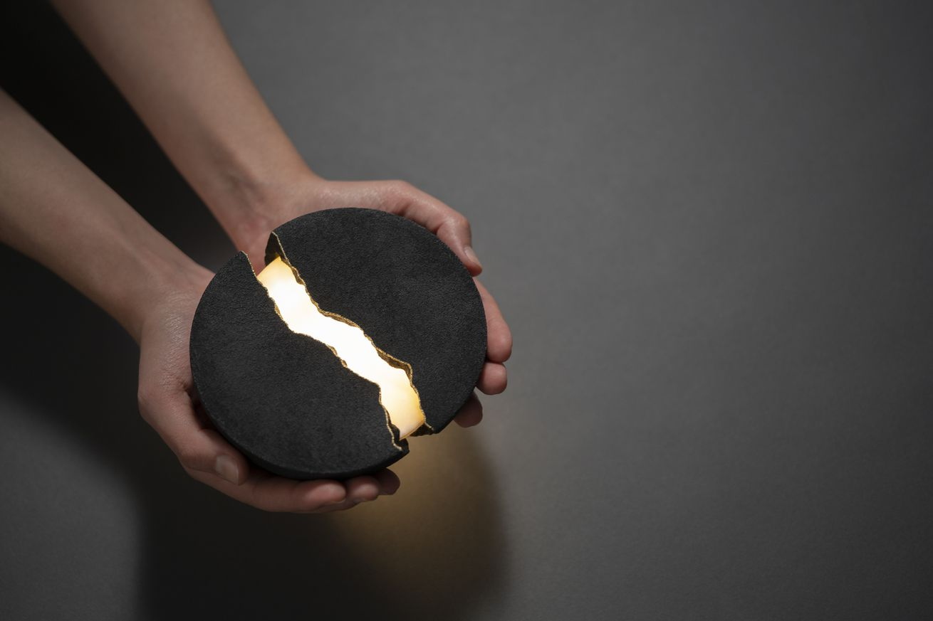 A pair of hands holding a small speaker that looks like a stone that's been cracked open with light coming out from it's center.