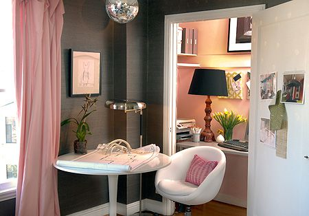 A closet is turned into an office and painted light pink.