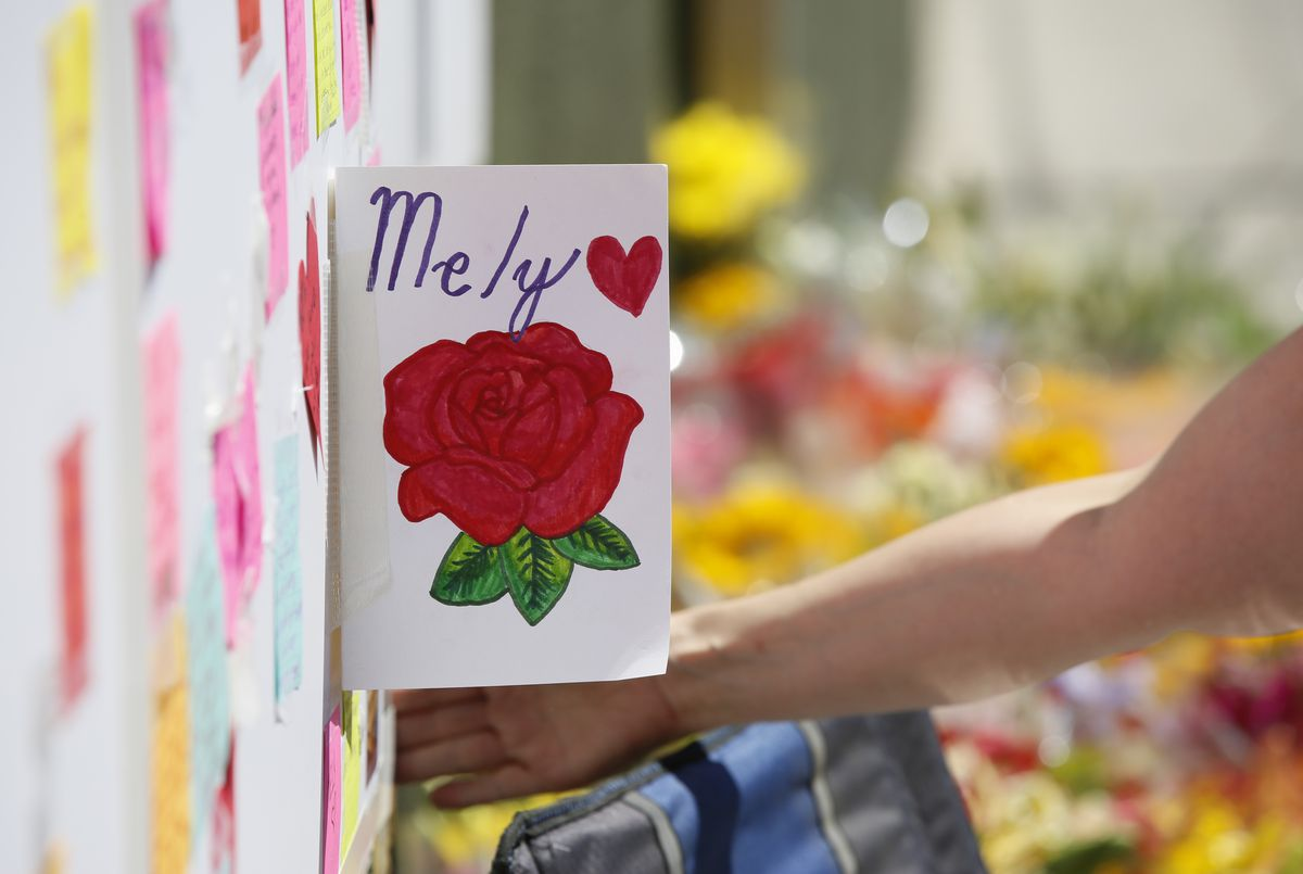 A card for Trader Joe's employee Melyda Corado, who was shot and killed a day earlier at the store by a suspect being chased by police, hangs at a makeshift memorial, outside the Los Feliz Trader Joe's supermarket in Los Angeles July 22, 2018. | AP Photo/