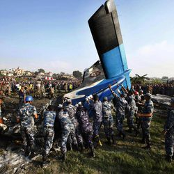 Nepalese police search move the remains of a Sita Air airplane at the crash site near Katmandu, Nepal, early Friday, Sept. 28, 2012.  The plane carrying trekkers into the Everest region crashed just after takeoff Friday morning in Nepal's capital, killing all 19 people on board, authorities said.