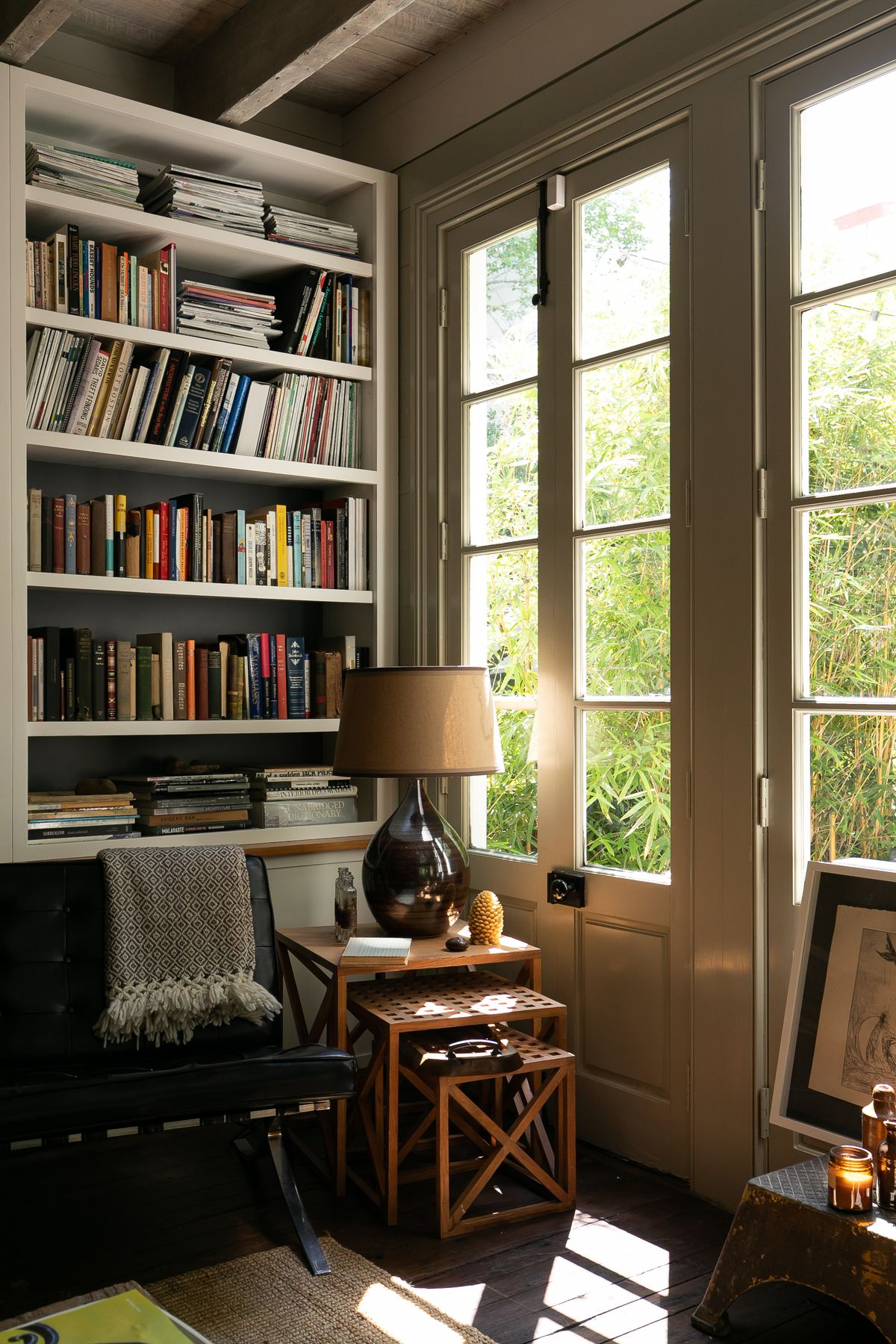 A corner of a living room with a bookcase full of books, a table with a lamp, and a couch. There are glass paned windows on the wall overlooking trees.