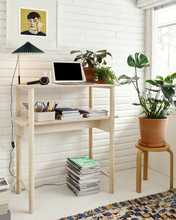Blonde wood standing desk surrounded by plants.