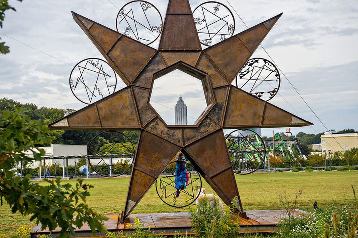 """Jacklyn Dashnaw climbs Charlie Smith's piece for Art on the Beltline 2015, """"A 24/7 Timestar Lives."""""""