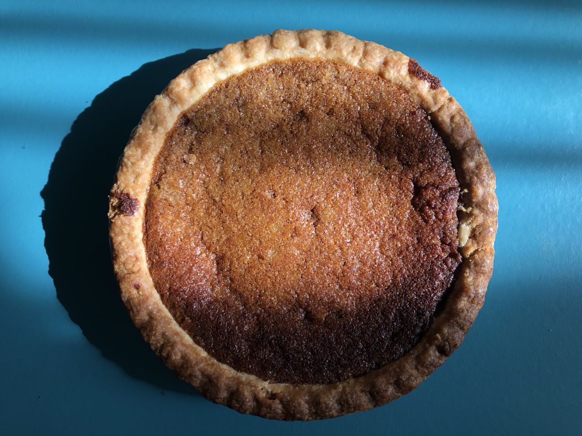 A brown pie with a light brown crust is set on a sunny teal blue table