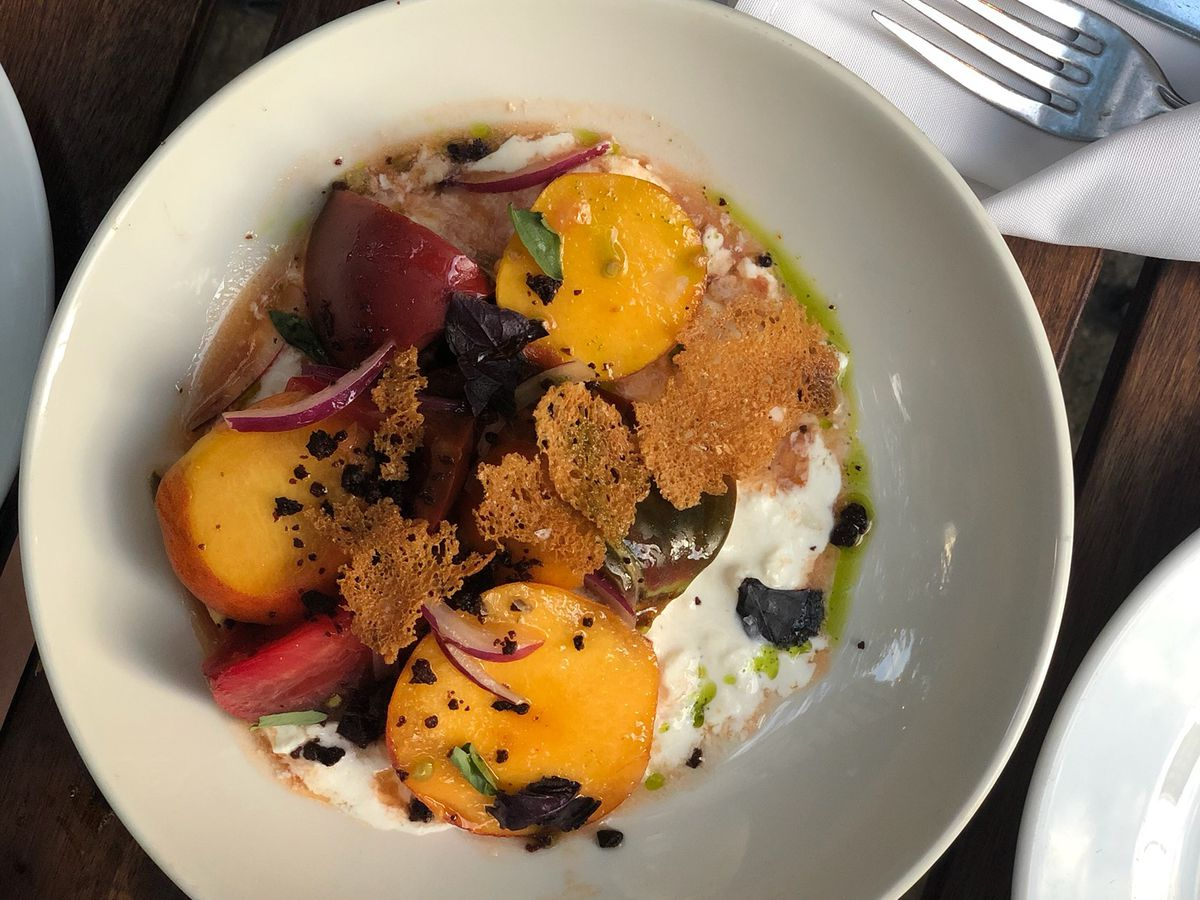 Heirloom tomatoes, red onion, burrata, and a green oil are mixed together in a white bowl
