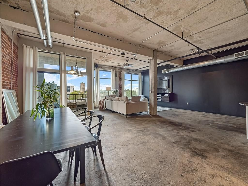 A large dining table on concrete with a concrete ceiling.
