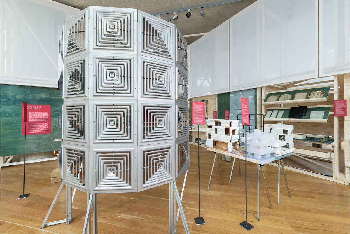 A cylindrical structure made of metal panels stands in the exhibition space.