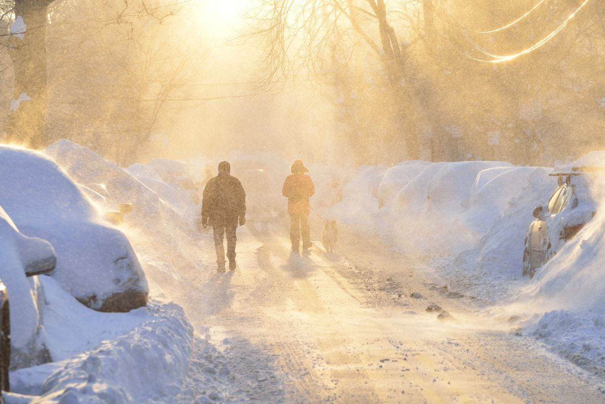 Two people trudging through a blizzard in Boston.