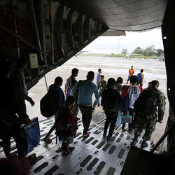 People walk off a military transport airplane in Cebu City, Philippines after leaving Tacloban, Wednesday, Nov. 20, 2013, following Typhoon Haiyan.
