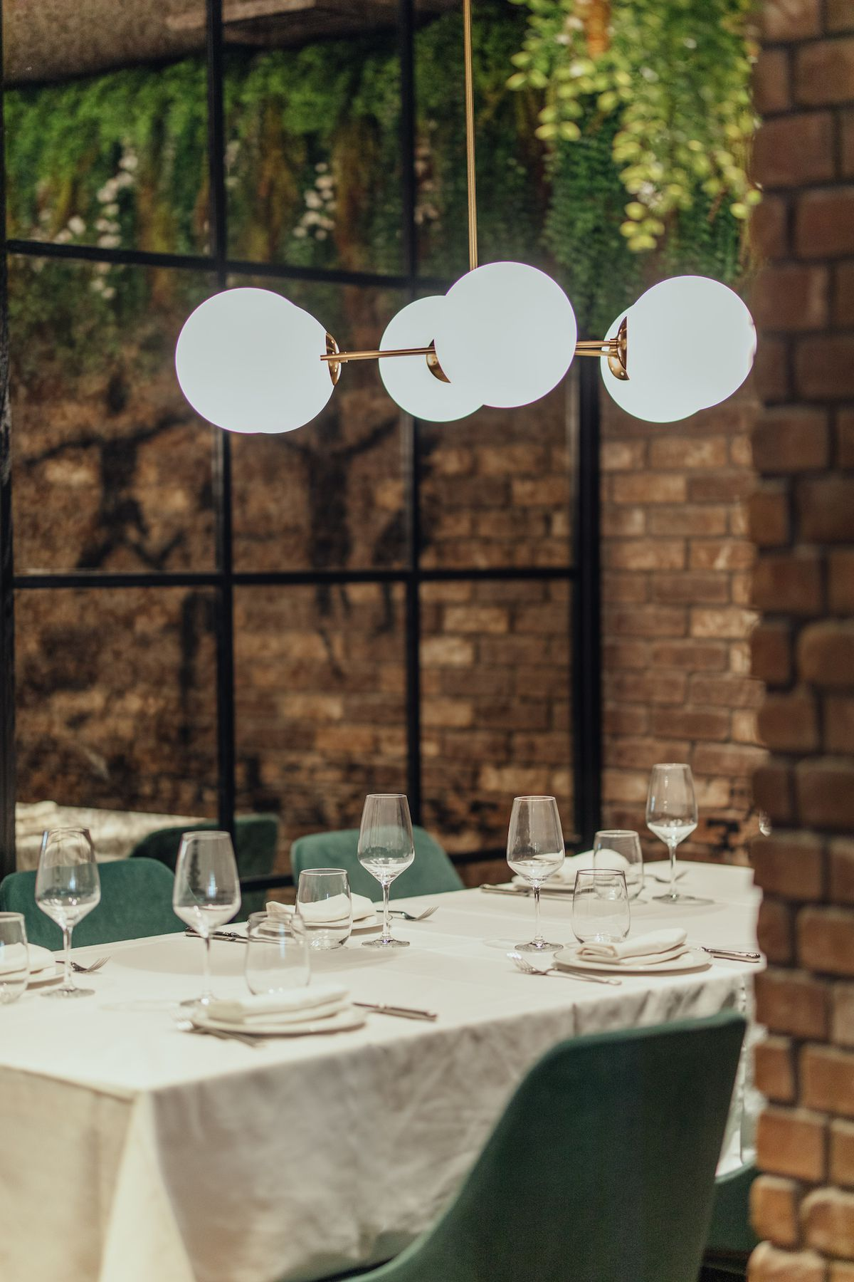 A vertical photo of a new brick and white tablecloth restaurant with lots of greenery.