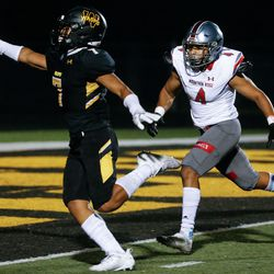 Wasatch's La'a Kalama, left, completes a touchdown during the fourth quarter of a high school football game against Mountain Ridge on Friday, Aug. 27, 2021, at Wasatch High School in Heber City. Mountain Ridge won 40-30.