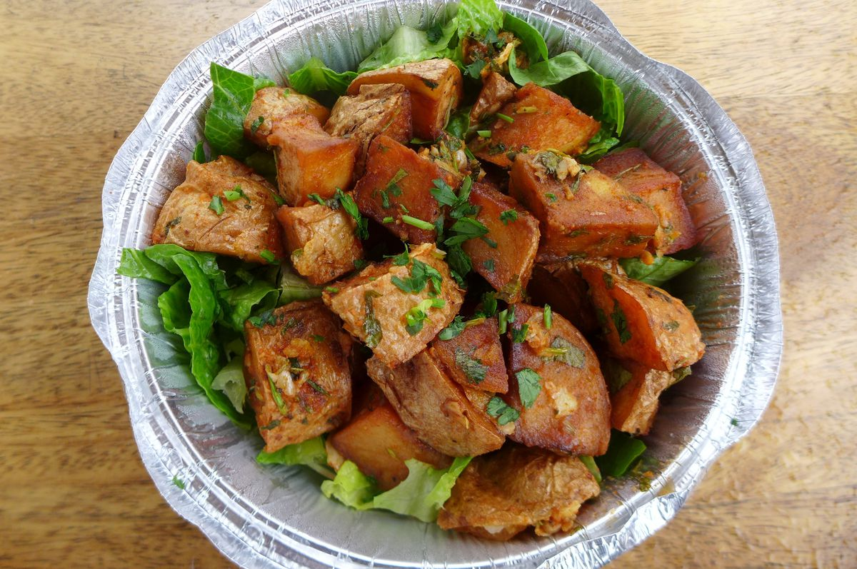 Big chunks of browned potato in a round aluminum carryout container.
