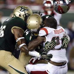 Rutgers' Mason Robinson (24) loses his helmet after a hit by South Florida's Fidel Montgomery (14) and Mark Joyce, left, on a first-quarter attempted punt return during an NCAA college football game Thursday, Sept. 13, 2012, in Tampa, Fla. Robinson fumbled the football and South Florida recovered.