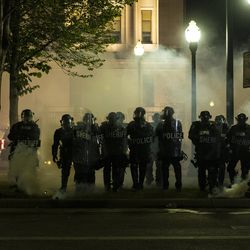 Police advance on protesters in Civic Center Park through a curtain of smoke during a protest over the shooting of Jacob Blake, Tuesday, Aug. 25, 2020, in Kenosha, Wis.
