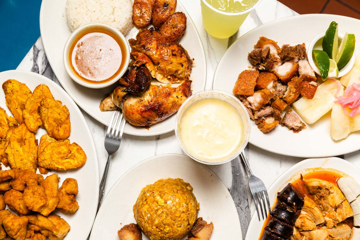 A spread of dishes sit on a table, including fried platanos, rotisserie chicken, chicharrones Dominicano, and a morir soñando drink