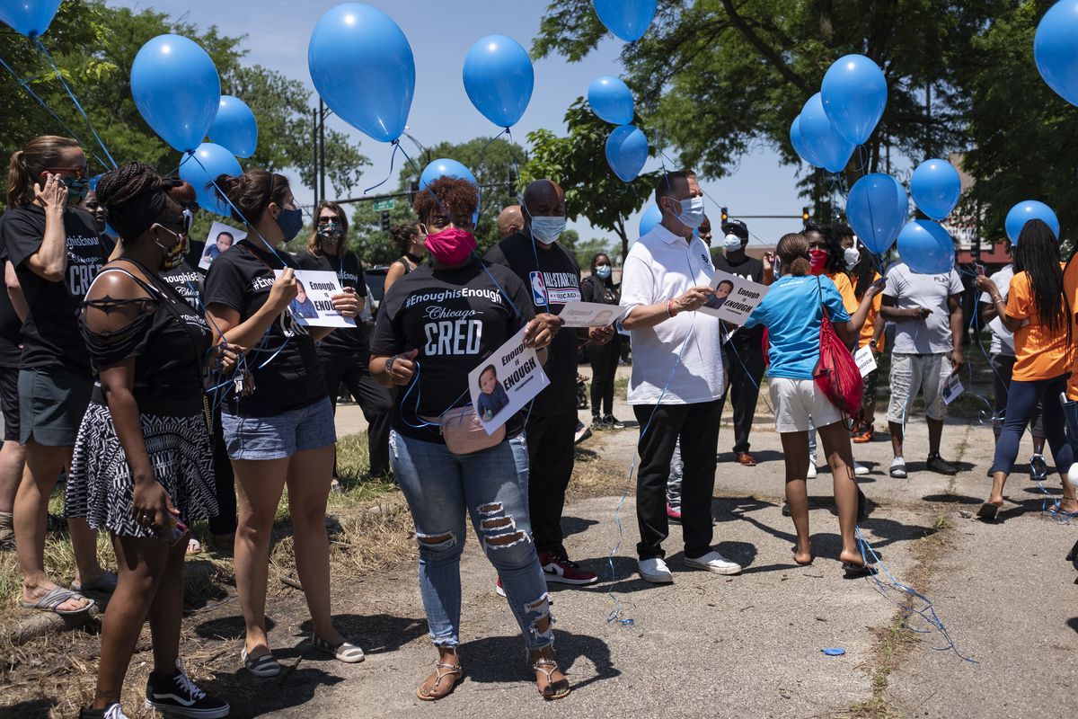 Friends and family hold balloons and sign during a vigil for Sincere A. Gaston on Wednesday.