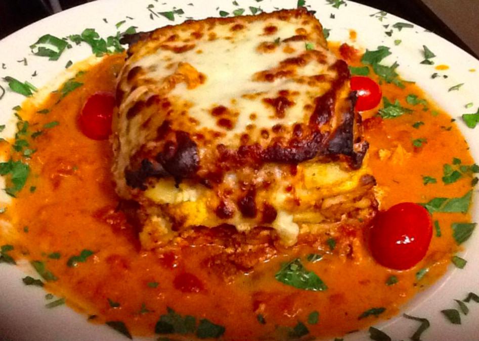 A lasagna-style dish is topped with brown cheese and sits in a tomato sauce with a sprinkling of parsley