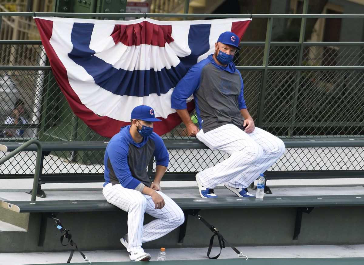 Chicago Cubs starting pitcher Jon Lester, right, watches an opening day baseball game against the Milwaukee Brewers from the bleachers during the first inning, Friday, July, 24, 2020, in Chicago.
