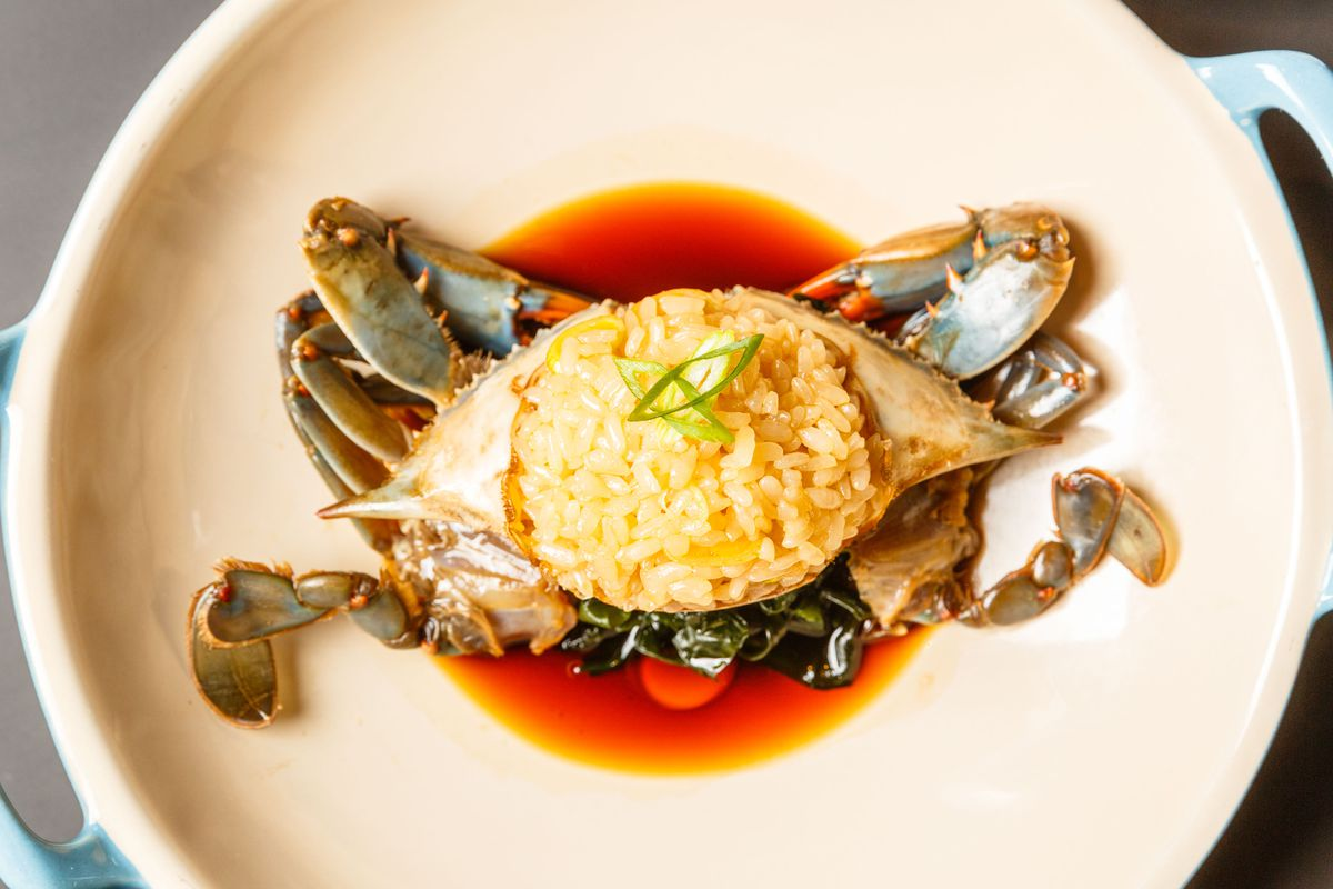 Raw blue crab sits in a pool of soy at Kawi