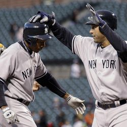 New York Yankees' Derek Jeter, right, greets Curtis Granderson at home plate after Jeter scored on Granderson's home run in the first inning of a baseball game against the Baltimore Orioles in Baltimore, Wednesday, April 11, 2012.