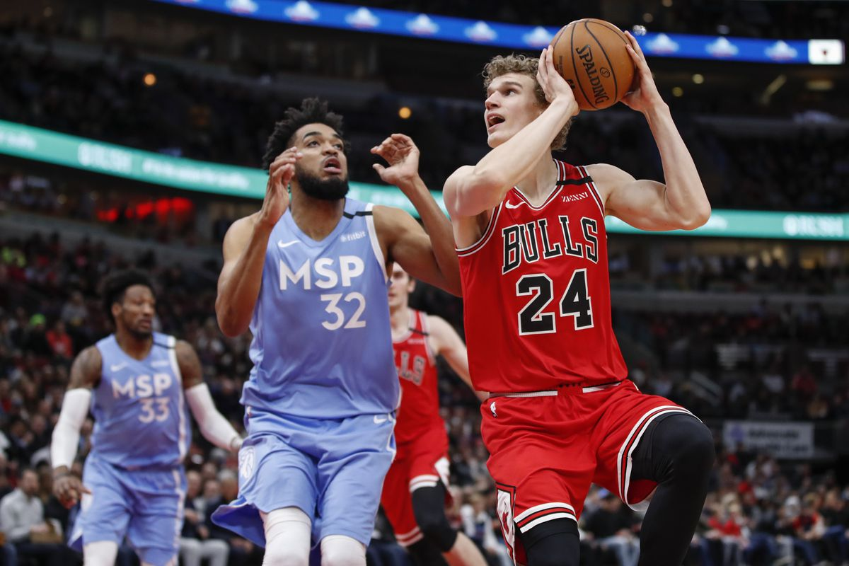 Chicago Bulls forward Lauri Markkanen shoots against Minnesota Timberwolves center Karl-Anthony Towns during the first half at United Center.