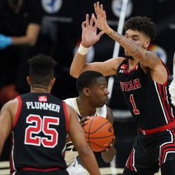 Colorado guard McKinley Wright IV, center, tries to slips between Utah guard Alfonso Plummer, front, and forward Timmy Allen for a shot in the second half of an NCAA college basketball game Saturday, Jan. 30, 2021, in Boulder, Colo. Utah won 77-74. (AP Photo/David Zalubowski)