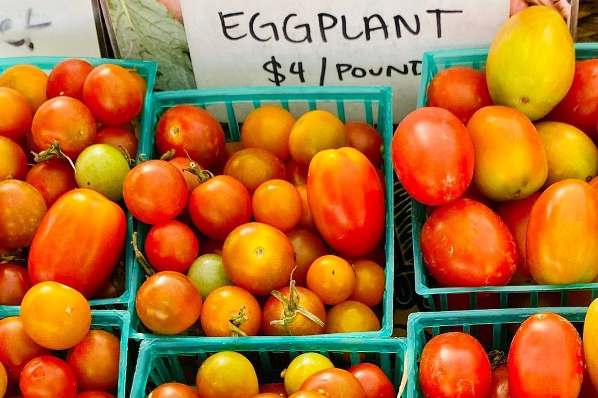 a bunch of cherry tomatoes at a farmer's market and sign for eggplants on sale