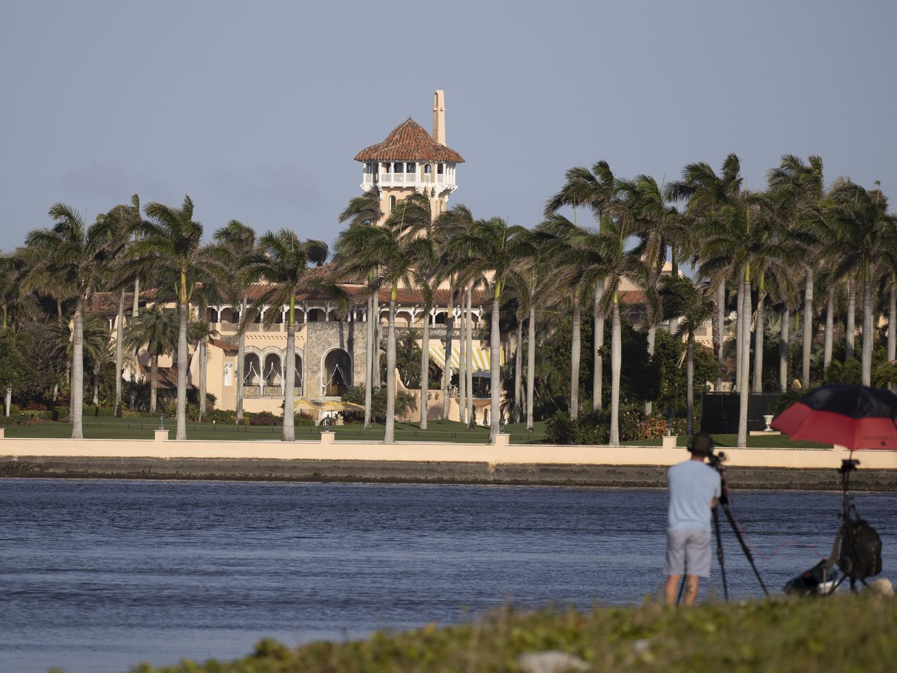 Mar-a-Lago resort in Palm Beach, Florida, as seen from across the Intracoastal Waterway. A man stands in the foreground with a camera on a tripod.