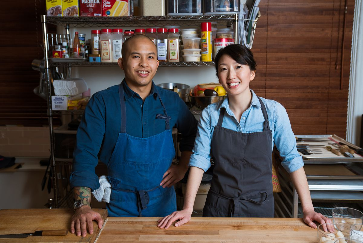 Two smiling people both wearing aprons, one with a shaved head, standing next to each other with their hands on a light wooden counter in a kitchen.
